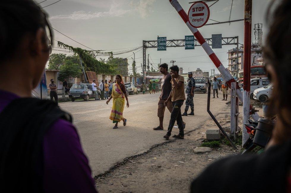 Dos vigilantes de frontera de una ONG contra el tráfico de personas (derecha e izquierda) examinan a las personas atraviesan a pie el paso fronterizo de la ciudad nepalí de Bhairahawa para intentar interceptar y rescatar a las víctimas de trata e impedir que entren en India. rnrn Las ONG contra el tráfico de personas tienen diferentes ideas sobre si la frontera debe seguir totalmente abierta o si ambos países deberían acordar establecer más controles y restricciones a la emigración. Aunque está demostrado que combatir la trata es una batalla difícil, muchos también opinan que la emigración es un derecho, y que la libertad de movimiento es fundamental para la economía de las poblaciones de frontera y para Nepal en general. Miles de nepalíes utilizan esta ruta a diario para trabajar al otro lado de la frontera con India.