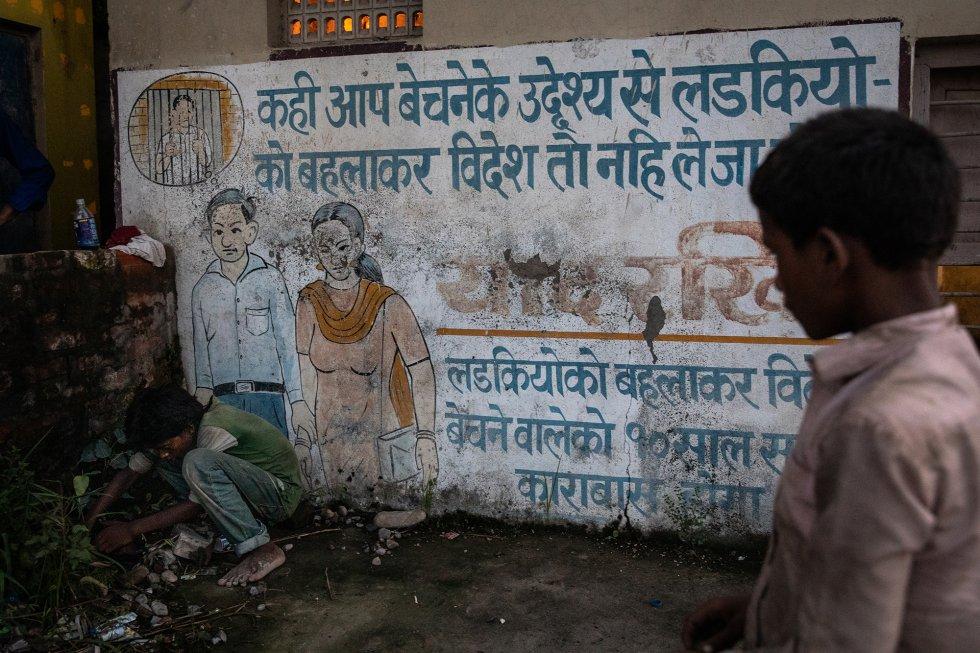 Dos niños juegan a las canicas junto a un mural en la frontera entre India y Nepal que advierte a las mujeres de los peligros de la trata de personas y, en concreto, de que si acompañan a alguien que promete un trabajo al otro lado de la frontera, en realidad podrían estar cayendo en una trampa para venderlas. En Bhairahawa, Nepal. rnrn Sin embargo, casi la mitad de las mujeres nepalíes (46,9%) pueden tener problemas para leer el mural. Según el World Factbook de la Agencia Central de Inteligencia (CIA) de Estados Unidos, en Nepal solo el 53,1% de las mujeres mayores de 15 años sabe leer y escribir, mientras que entre los hombres la tasa es del 76,4 %. Los elevados niveles de analfabetismo también son una de las causas de que muchas mujeres sean presa fácil de los traficantes. En cambio, en los grandes vecinos de Nepal, las tasas de alfabetización de las mujeres son del 60,6 % en India y del 94,5 % en China. Dado que la gran mayoría de las víctimas del tráfico de personas en el mundo ‒alrededor del 71%‒ son niñas y mujeres, y un tercio son menores de edad, la alfabetización femenina es fundamental.
