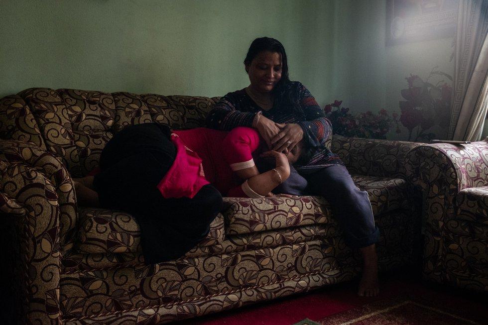 Sunita Danwuar (derecha), de 41 años, cubre la cara de T., de 30, ambas supervivientes del tráfico de personas. Las dos mujeres posan en la casa de Danwuar en Katmandú, capital de Nepal. Ambas se han prestado apoyo mutuo y han ayudado también a otras supervivientes de la trata con fines sexuales. T., que sobrevivió a las violaciones, el maltrato y la esclavitud en Kuwait, actualmente colabora con Danwuar, también superviviente y pionera de la lucha contra el tráfico de mujeres desde Nepal. Tras ser secuestrada a los 14 años y prostituida durante cuatro en un burdel de Bombay, Danwuar fue rescatada, y junto con otras mujeres y niñas liberadas de India como ella fundó la ONG Shakti Samuha (Grupo de Poder) contra la trata de personas. Actualmente dirige su propia fundación, dedicada a devolver la confianza a las supervivientes del tráfico ilegal. Apenas alfabetizada, sin haber superado el trauma y profundamente estigmatizada por haber sido víctima del tráfico, Danwuar logró rehacer su vida liderando la lucha contra el tráfico sexual en Nepal y dando educación a su hija en un país en el que solo el 53,1% de las mujeres de más de 15 años saben leer y escribir. La Organización Mundial del Trabajo de Naciones Unidas advierte de que hay más de 40 millones de esclavos en el mundo. La gran mayoría de las víctimas del tráfico ‒alrededor del 71 %‒ son mujeres y niñas, y un tercio son menores de edad.