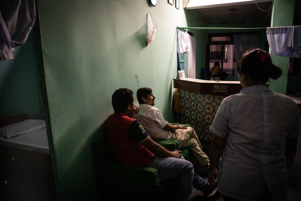 """Una trabajadora (derecha) habla con dos clientes (izquierda) en un salón de """"sasaje"""" ‒el nombre coloquial con que se conoce a los salones de masaje que sirven de tapadera a un burdel, en los que los servicios sexuales se prestan en el mismo establecimiento‒ que esperan su turno en la zona turística de Katmandú, capital de Nepal. rnrn Esta es una de las razones de que el peligro también aceche en el propio país. Muchas de las víctimas de la trata no atraviesan la frontera internacional, sino que son atraídas a otros lugares de Nepal, generalmente desde las zonas rurales a las metrópolis, por conocidos que les prometen un trabajo como camarera o trabajadora doméstica en la capital. En realidad, las mujeres acaban obligadas a prostituirse en restaurantes o bares con bailarinas o reservados, o en salones de masaje, entre otros establecimientos que ofrecen servicios sexuales en grandes ciudades como Katmandú, capital de Nepal. rnrn Según el Manual para Responsables Políticos (Handbook for Decision Makers) sobre Tráfico y Explotación en los Sectores del Ocio y el Sexo en Nepal de la organización Terre des Hommes, las niñas y las mujeres han declarado que """"no se les permite abandonar su actividad hasta que traigan a una o más niñas para sustituirlas, lo cual las obliga a desempeñar el papel del proxeneta o el traficante"""". rnrn Algunas mujeres y niñas también están obligadas por la deuda originada por los pagos """"adelantados"""" hechos por los traficantes a su familia o al secuestrador (como ocurre con las niñas llevadas ilegalmente a India). En realidad, los anticipos son los pagos que las familias u otras personas reciben por entregar o vender a la niña y, en muchos casos, su virginidad. Otras víctimas contraen la deuda por los préstamos que toman de los traficantes para pagar el alojamiento, la comida o el teléfono móvil. rnrn Diversos organismos internacionales han clasificado a Nepal como """"país de origen"""" del tráfico de personas. En consecuencia, la investigación y la info"""