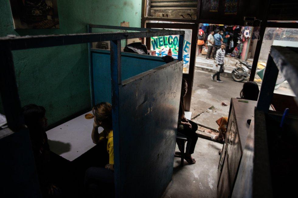 """En una zona menos turística de la capital, Katmandú, lo que se conoce en la ciudad como un """"restaurante con reservados"""" ofrece a los clientes la compañía de las camareras para pasar un rato íntimo con ellas en las cabinas. Salta a la vista que muchas de las chicas son menores de edad. rnrn Los restaurantes con reservado ofrecen pequeños espacios privados, separados por mamparas de contrachapado, en los que las camareras tienen que entretener a los clientes y persuadirlos para que consuman bebidas alcohólicas y comida a precios exagerados como pago por sus servicios sexuales. Por entretenimiento se entiende desde la conversación hasta los besos, las caricias, la masturbación o el sexo oral. Por lo general, en la parte trasera hay una habitación que los clientes pueden usar para tener relaciones sexuales con la camarera. Otra posibilidad es ir a un hotel cercano para encuentros más largos. rnrn La mayoría de los restaurantes con reservado no cocina su propio menú. La comida se compra a establecimientos cercanos en los que el cliente podría comer a un precio normal. Los clientes van a los restaurantes con reservado por las camareras. rnrn Un estudio sobre estos establecimientos nepalíes realizado por la ONG Terre des Hommes descubrió que """"más de la mitad de las informantes declaraba que los propietarios las obligaba a realizar actividades contra su voluntad bajo la amenaza de despedirlas, hacerles daño, chantajearlas o difamarlas. Según otro estudio, tres cuartas partes de las trabajadoras fueron obligadas a realizar tareas adicionales, la mayoría de las cuales incluían tener relaciones sexuales con el cliente en una cabina o un hotel""""."""