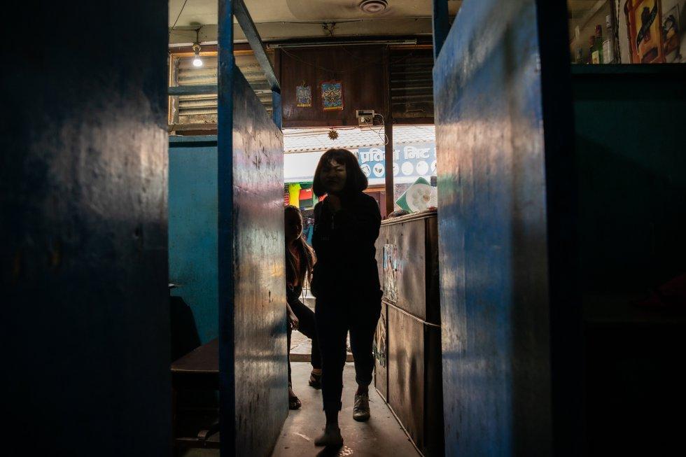 """Una camarera camina por un pasillo que conduce a varias cabinas separadas por mamparas de contrachapado en uno de los """"restaurantes con reservado"""", como se conoce en Nepal a los establecimientos de la capital, Katmandú, en los cuales los clientes pasan ratos íntimos con ellas en una cabina. En ellos, los servicios sexuales se venden directamente, y las instalaciones ofrecen pequeños compartimentos privados para caricias íntimas, masturbación o sexo oral. En Nepal, toda una industria secundaria gira en torno a los negocios del ocio y el sexo. Los restaurantes cercanos proveen los platos que aparecen en los menús de estos establecimientos. La mayoría de los restaurantes con reservado no cocinan la comida que ofrecen, sino que la compran en las proximidades. El reclamo de los restaurantes con reservado son las camareras. Los hoteles cercanos sirven a los clientes de los restaurantes con reservado que quieren tener un encuentro sexual más largo con la camarera. Se calcula que gran parte de las trabajadoras de los sectores de la hostelería y el ocio son víctimas del tráfico de personas. Sin embargo, el alcance real es difícil de determinar debido a que las mujeres y las niñas son aleccionadas para que mientan a los trabajadores sociales sobre su edad y su situación por miedo a las represalias de los propietarios y los gerentes de los negocios."""