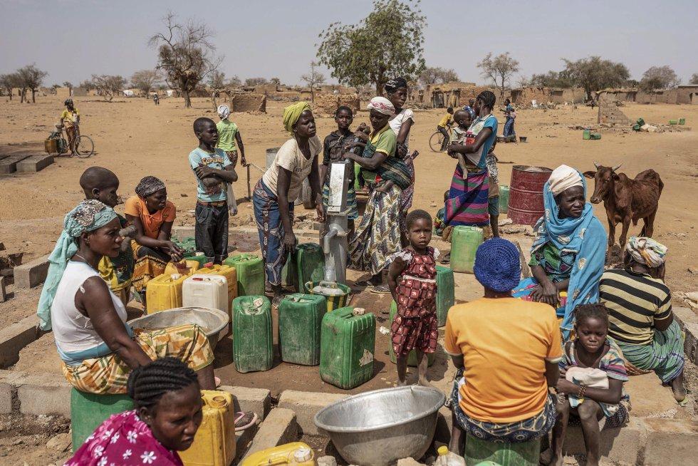 Burkina Faso ya ha superado el millón de personas desplazadas a causa de la escalada de violencia que sufre el país según las estadísticas publicadas por las autoridades nacionales. Esto supone un aumento del 8,62% desde abril de 2020, y más del triple que cuando se aprobó la primera estrategia de agrupación de refugios hace casi un año. Uno de cada 20 habitantes está desplazado a causa de esta crisis humanitaria, lo cual representa un 5% de la población total del país. Desde el comienzo de la pandemia, el número de personas que padece inseguridad alimentaria en Burkina Faso, Mali y Níger ha aumentado en un millón, llegando a los 4,8 millones de afectados. Esta cifra podría duplicarse o incluso triplicarse, ya que el virus sigue propagándose y las medidas de bloqueo afectan a los más vulnerables según afirma un estudio del CSIS. En la imagen, mujeres y niños hacen cola para recoger agua con sus bidones amarillos en un punto de agua potable del campo de desplazados internos de Barsalogho en marzo de 2020.