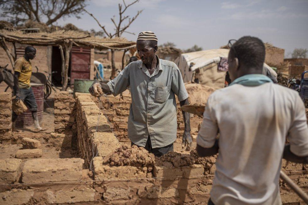 Varias personas desplazadas construyen una casa en el campo de refugiados de Barsalogho en marzo de 2020. Según los administradores locales, la población ha aumentado notablemente debido a la gente que huye de los ataques sufridos en las localidades más pequeñas de la región. Barsalogho se encuentra en el centro norte del país, una de esas zonas que han sufrido ataques repetidos en los últimos años.