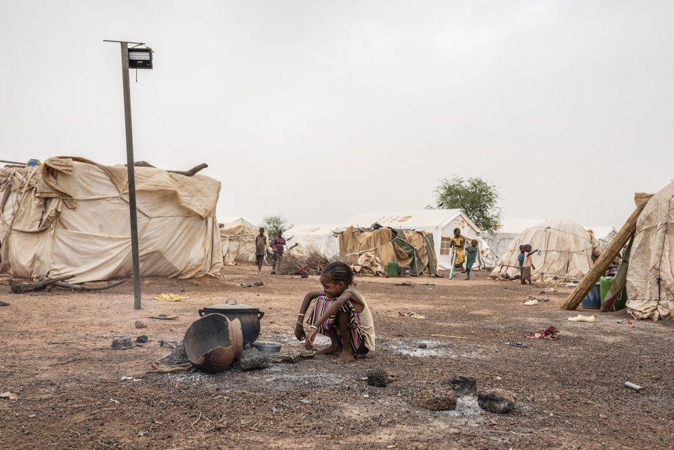 Las regiones del centro-norte y del Sahel siguen siendo las más afectadas del país, con el 46,1% y el 37,0%, respectivamente, del total de la población desplazada registrada. Les siguen el Norte (7,5%), el Este (2,2%) y la región de Boucle de Mouhoun (1,7%). Los refugiados también buscan cobijo en otras regiones del país, como la Meseta Central (0,8%) y Hauts-Bassins (1,2%). En la imagen, una niña sonríe frente a un caldero puesto al fuego en Barsalogho.