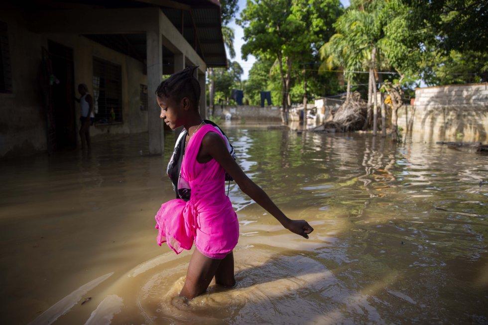 Una niña camina hacia su casa inundada un día después del paso de 'Laura', en Puerto Príncipe Haití.