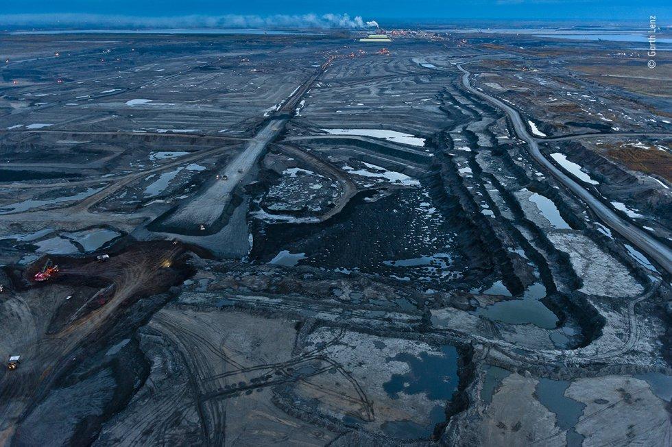A medida que cae el crepúsculo sobre las arenas bituminosas de Alberta (Canadá), el paisaje adquiere un tinte azul. Esta vasta extensión, que alguna vez fue un bosque boreal, es solo una sección de la mina de arenas bituminosas de Mildred Lake, solo una de las muchas minas de la región que conforman la tercera reserva de petróleo más grande del mundo.