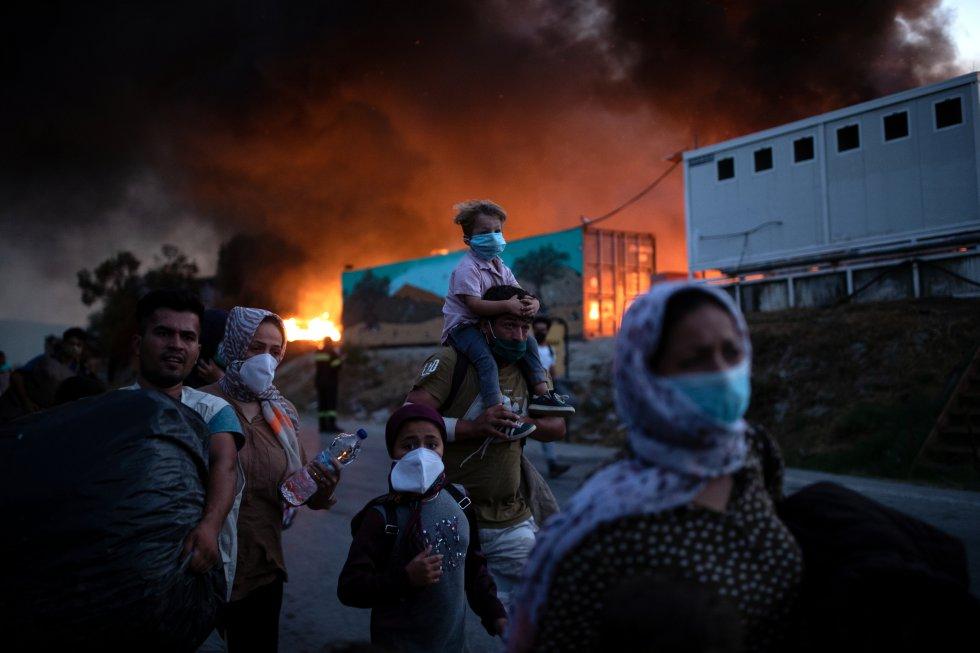 Un segundo incendio ha sido declarado este miércoles en el campo de refugiados de Moria, afectando a zonas que no habían sido alcanzadas por las llamas hasta ahora. En la imagen, varios refugiados abandonan el campo de Moria con algunas pertenencias. A sus espaldas, una gran columna de humo.
