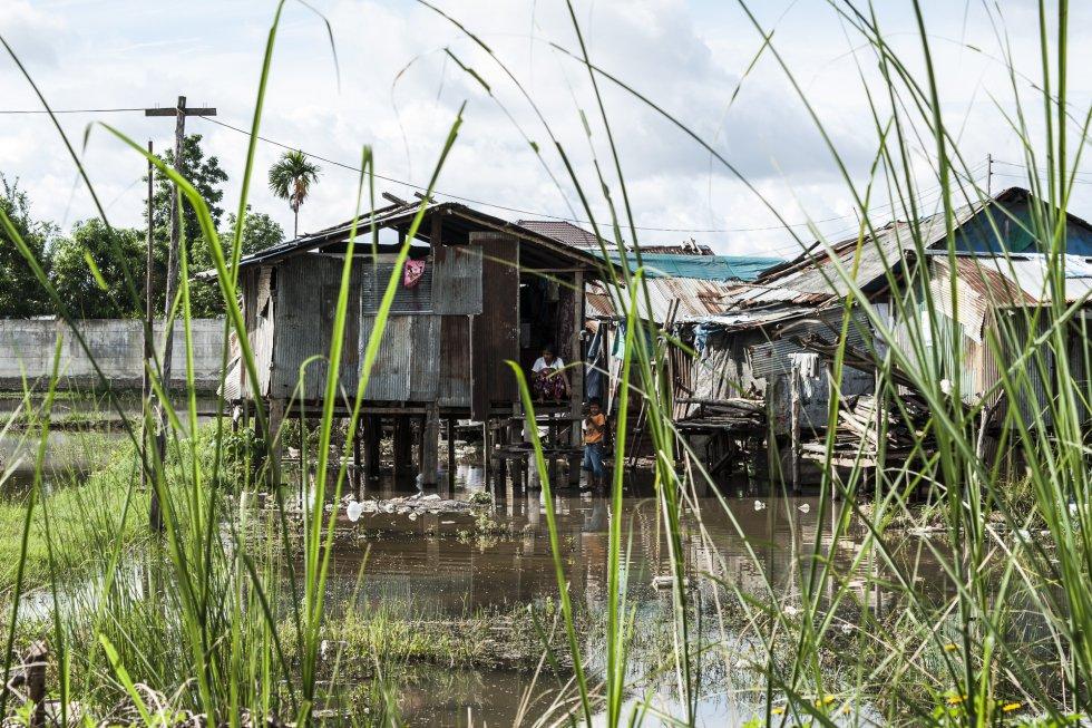 """Una vista del barrio donde vive Sandar, en las afueras de Mae Sot. Sandar procede de Mawlamiyaing, una ciudad birmana situada a 130 kilómetros de Mae Sot. La joven entró ilegalmente en Tailandia cuando tenía 15 años. La larga frontera de la zona de Mae Sot, en la que los dos países están separados solamente por un río, la convierte en el lugar perfecto para que los birmanos entren ilegalmente en Tailandia. En los últimos tiempos, las autoridades tailandesas han intensificado los controles fronterizos debido al aumento del número de casos de covid-19 en Myanmar. Mae Sot es una zona principalmente rural. Muchos emigrantes birmanos están empleados en la agricultura, y a menudo cobran menos del salario mínimo. Con ocasión del Día Internacional de la Mujer Rural el pasado 15 de octubre, ONU Mujeres subrayó este año """"la urgente necesidad de fomentar la capacidad de resistencia de las mujeres rurales tras la covid-19 reforzando su bienestar y unos medios de vida sostenibles con el fin de 'reconstruir mejor""""."""