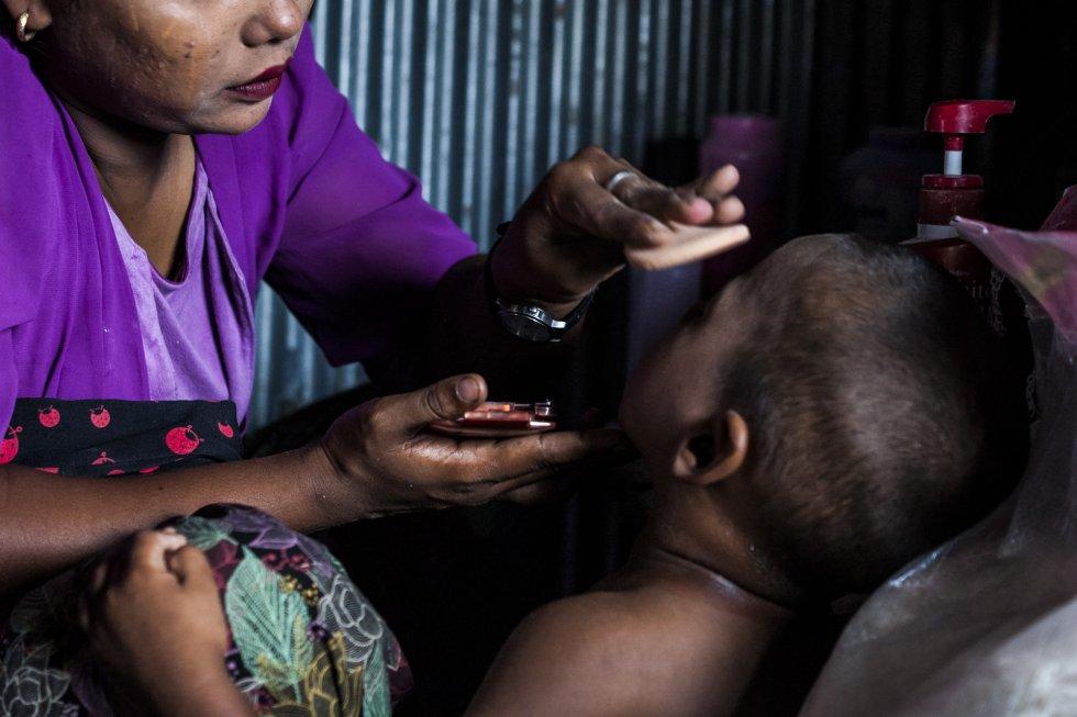Sandar pone 'thanaka' a su hijo menor en la cara antes de salir. El 'thanaka' es una pasta cosmética de color blanco amarillento hecha a base de corteza molida que las mujeres birmanas suelen emplear para suavizar la piel y protegerla del sol.