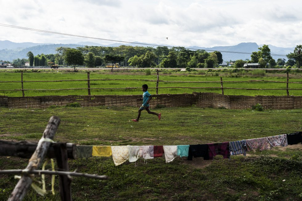 """El hijo mayor de Sandar, de nueve años, corre por un campo cercano a su casa, en las afueras de Mae Sot. El niño se queda en casa mientras su madre y su hermano menor van al centro de detención. El Proyecto Restauración de la Libertad organiza clases de crianza para enseñar métodos educativos alternativos a las víctimas de violencia doméstica. """"Les enseñamos que hay otras maneras [de educar a los hijos] que no son gritar y pegar"""", explica Watcharapon 'Sia' Kukaewkasem, fundadora y directora del proyecto. """"Cuando hablamos de violencia doméstica no nos referimos solo a la que ejerce la pareja, sino también a la de los padres contra los hijos. [...] Intentamos prevenirla""""."""