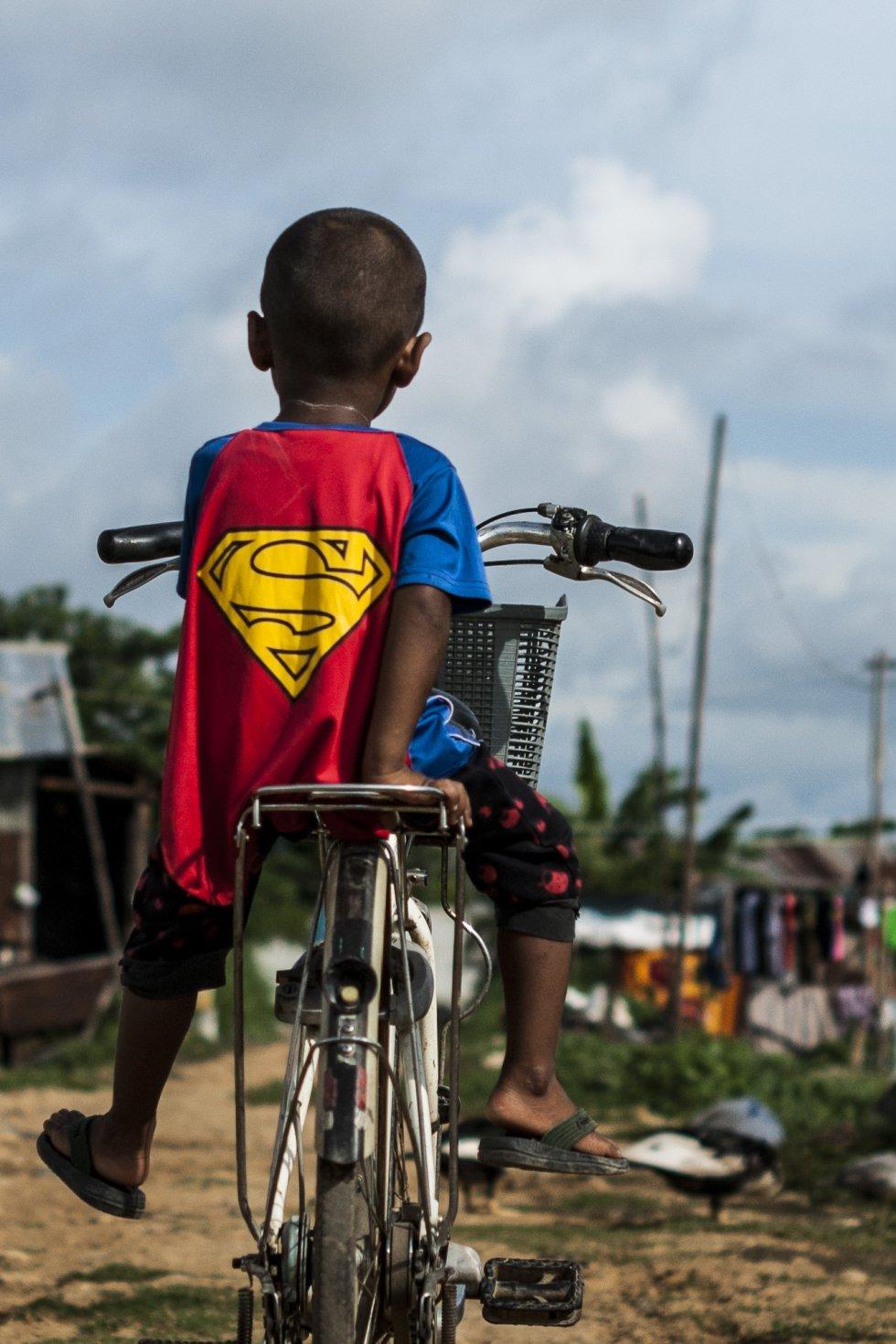 """El hijo pequeño de Sandar, de tres años, espera a su madre sentado en la bicicleta vestido con un traje de Superman. Van al centro de detención de Mae Sot a visitar a su padre. """"Me gustaría que mis hijos no tuviesen que trabajar tanto como yo"""", dice Sandar. """"Me gustaría que estudiasen y fuesen médicos o contables""""."""
