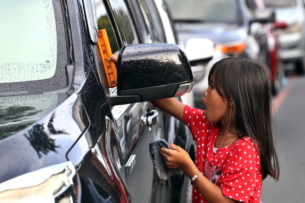 Los menores en Filipinas están en riesgo de permanente abandono escolar, un problema especialmente grave en el país asiático, donde 3,8 millones de niños no cursan enseñanza alguna y solo el 30 % de las personas en los barrios más pobres tienen estudios secundarios, según un informe del Banco Mundial. En la foto, una niña limpia parabrisas de autos en una céntrica avenida de Manila.