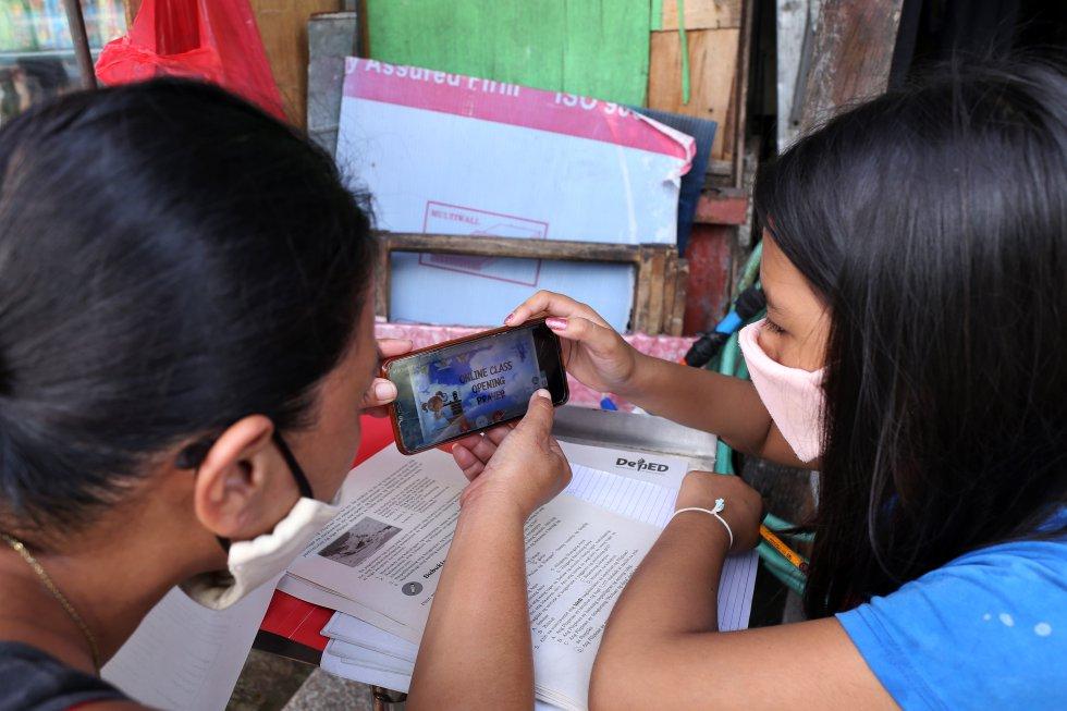 Christine Mae Escobido (derecha), de 11 años, y su madre Warlyn Langit estudian Geografía con la ayuda de un móvil en el barrio de Santa Ana, en Manila.