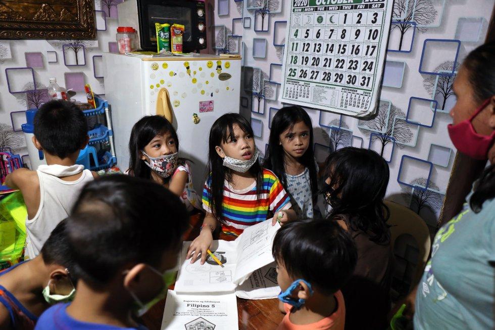 Un grupo de escolares se reúnen en casa de Nidia Iliena, en el barrio de Soldiers Hill, para estudiar con la ayuda de un teléfono celular que esta compró para sus hijos.