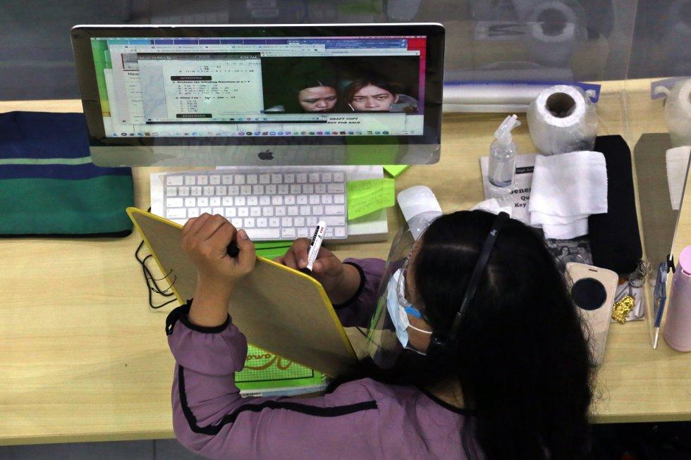 Una maestra miembro del programa Tele-Aral explica en una pizarra una lección a sus alumnos que se encuentran conectados a Internet.
