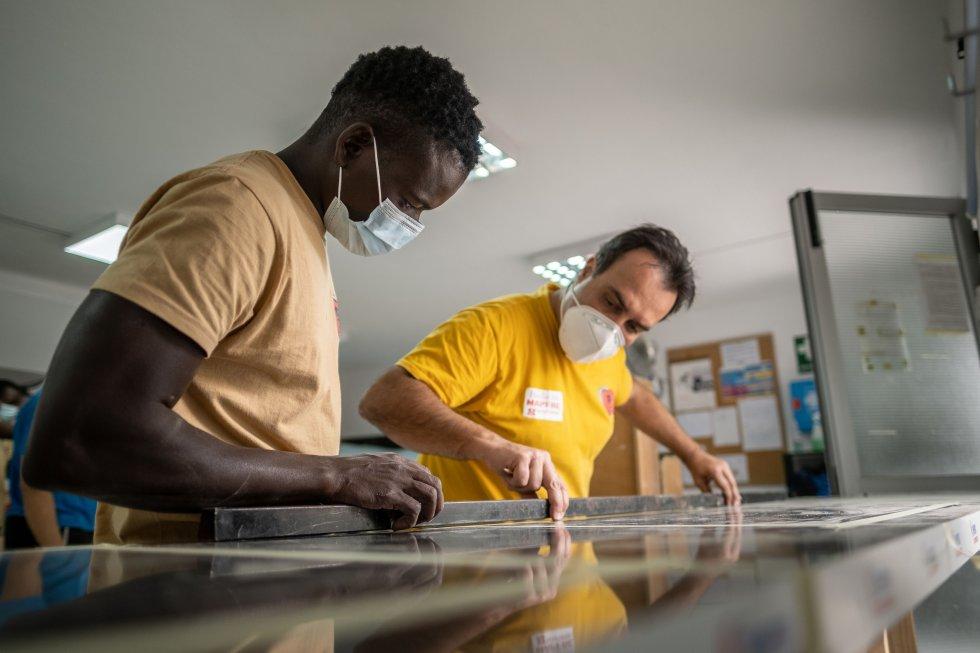 Malan y un compañero del curso de carpintería miden las piezas necesarias para el montaje de una cocina. Malan se esfuerza cada día en cumplir con los objetivos y perfeccionar sus técnicas pensando en dedicarse a este oficio en el futuro.