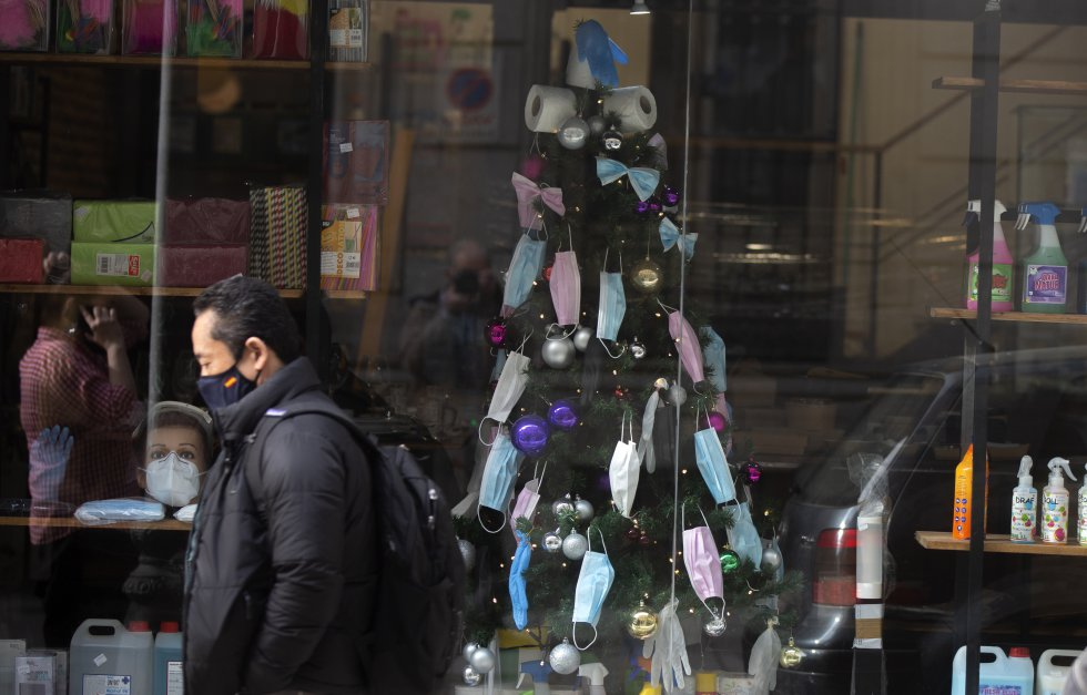 Un árbol de Navidad decorado con mascarillas, guantes de plástico y papel higiénico, en un escaparate de una tienda en el centro de Madrid (España), el 17 de diciembre.