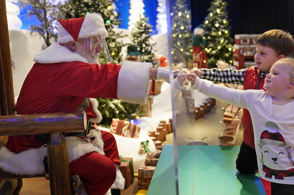 Dos niños saludan a un hombre vestido de Santa Claus a través de una mampara de metacrilato en un centro comercial en Bridgeport, Connecticut (EE UU), el 10 de noviembre.
