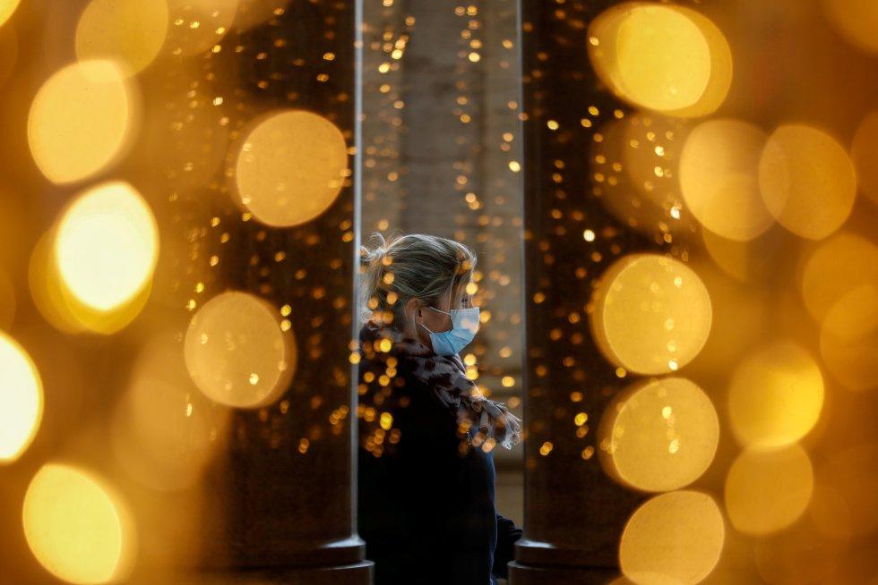 Una mujer con mascarilla, vista a través de las luces de Navidad en Roma (Italia), el 2 de diciembre.