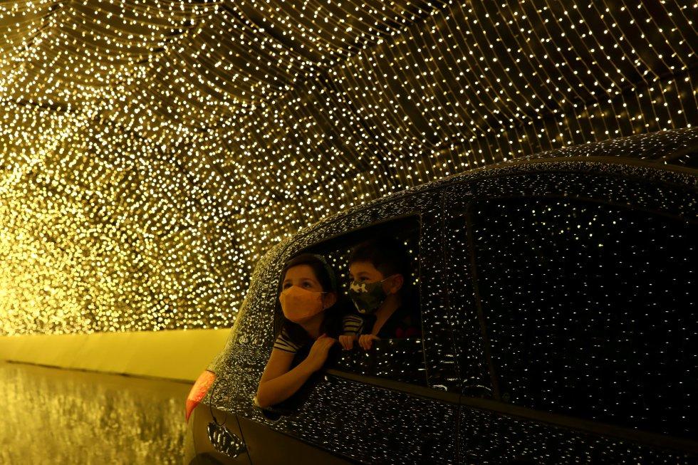 Dos niños miran las luces desde el interior de un vehículo mientras visitan Luminna Fest en São Paulo (Brasil), el 5 de diciembre.