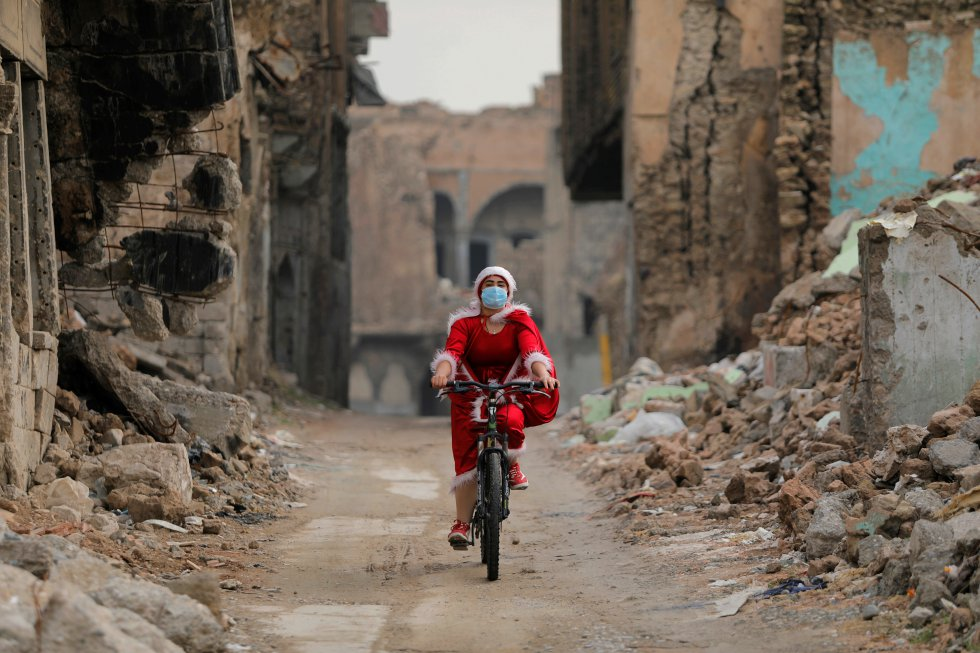 Una mujer vestida de Papa Noel monta en su bicicleta en la ciudad vieja de Mosul (Irak), el 18 de diciembre.