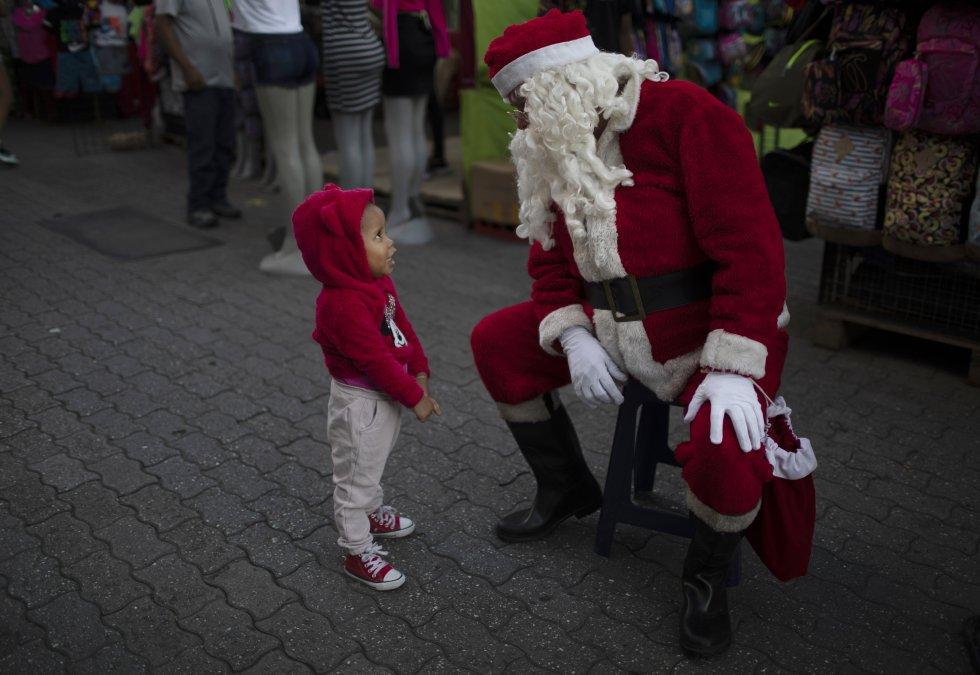 Fredy Parra, vestido como Santa Claus, habla con una niña en una feria navideña en Caracas (Venezuela), el 18 de diciembre.