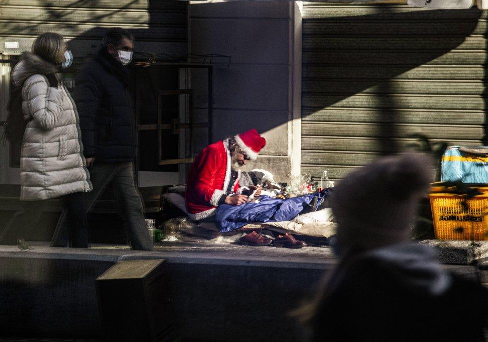 Una persona sin hogar vestido de Santa Claus se refleja en el escaparate de una tienda en Milán (Italia), el 13 de diciembre de 2020.