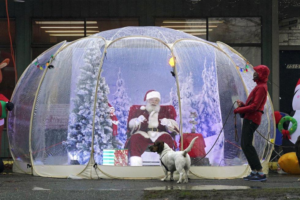 Un hombre vestido de Santa Claus permanece sentado en el interior de una burbuja de plástico en el vecindario de Greenwood en Seattle (EE UU), el 8 de diciembre.