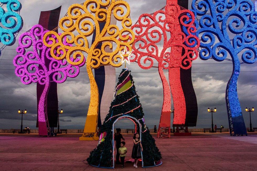 Una familia se prepara para hacerse una foto en la plaza Juan Pablo II de Managua (Nicaragua), el 17 de diciembre.