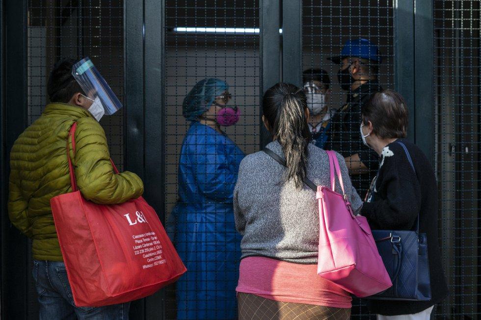 La puerta de urgencias por covid-19 del hospital La Raza reúne a familiares que esperan saber si hay camas disponibles para sus parientes. A la derecha, Guadalupe Vargas pide informes sobre su hermana María Socorro, ingresada este 23 de diciembre.