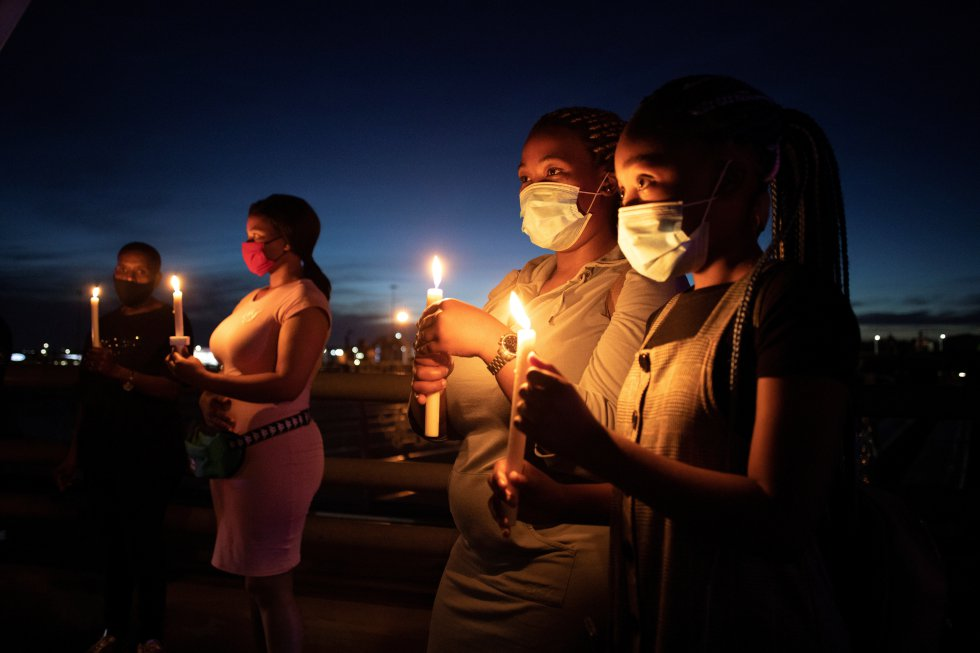 Grupo de pessoas presta homenagem às vítimas do coronavírus, na véspera de Ano Novo em Joanesburgo, na África do Sul.