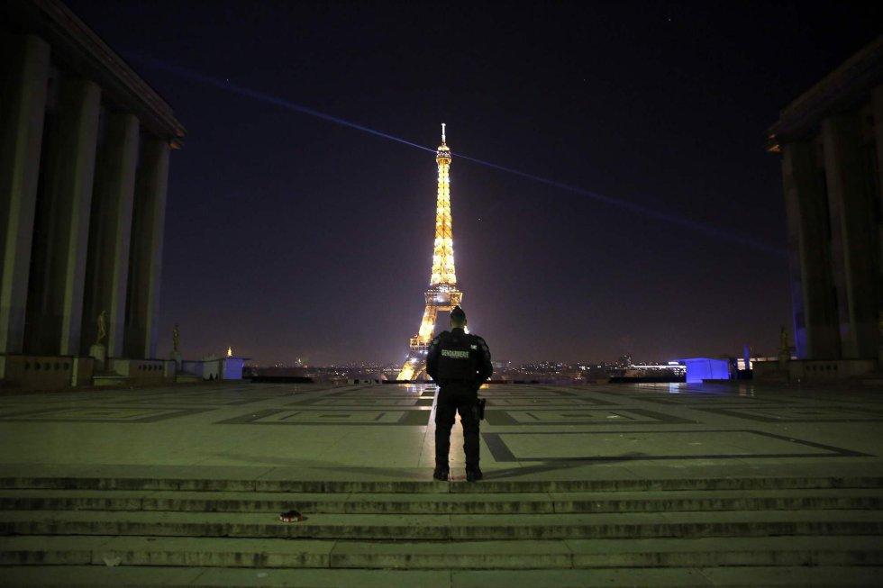 Policial patrulha a praça Trocadero em Paris. Ao fundo, a Torre Eiffel.