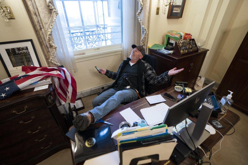 Un partidario del presidente de Estados Unidos, Donald J. Trump, se sienta en el escritorio de la presidenta de la Cámara de Representantes de Estados Unidos, Nancy Pelosi