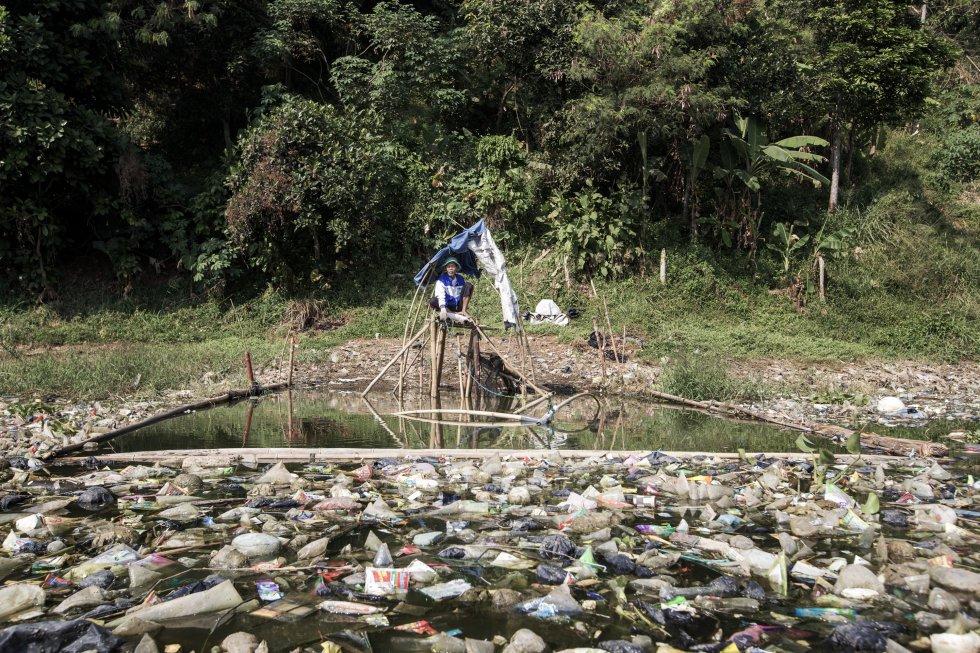 Uma pequena armadilha usada próxima a uma plataforma de bambu na margem do rio.  O lixo que flutua nas águas do Citarum, além de poluente, dificulta a tarefa.  Como os pescadores não têm alternativa para subsistir, eles constroem cercas flutuantes e pescam entre os escombros.