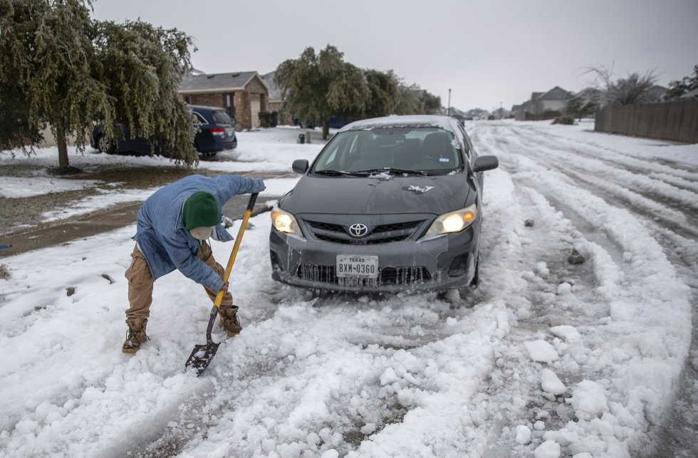 La tormenta provocó que las carreteras cerraran en el Estado. En la foto, un hombre intenta salir con una pala después de quedarse atascado en medio de la calle.