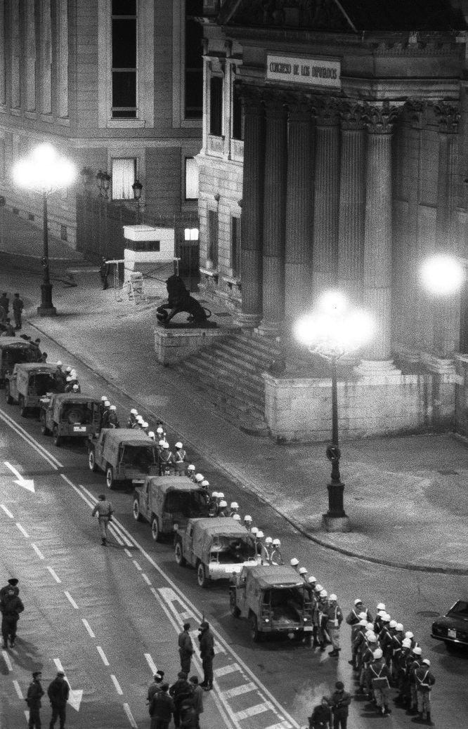 Aspecto que ofrecía el palacio del Congreso de los Diputados a las dos de la madrugada. Junto a las verjas del edificio (arriba en la foto) puede verse a tres miembros de la Guardia Civil. Alineados junto a sus vehículos, varias unidades de la Policía Militar que habían llegado con Ricardo Pardo Zancada (comandante de infantería que había intentado sin éxito que la División Acorazada Brunete se sublevara y sacar los tanques a las calles de Madrid, pero que consigue llegar al Congreso con un centenar de hombres de la Policía Militar). En primer término miembros del GEO. Hasta altas horas de la madrugada se había especulado sobre una posible intervención del Grupo Especial de Operaciones de la Policía en el rescate de los diputados. A las cinco de la madrugada, el comandante David Cervera, jefe del Estado Mayor de la Policía Nacional, negaba tal posibilidad en una rueda de prensa en el hotel Palace.