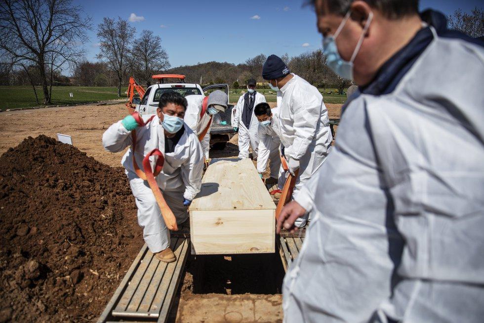 Coveiros baixam o caixão de vítima do coronavírus no cemitério da Associação Hebraica de Enterro Livre no distrito de Staten Island, em Nova York, em abril de 2020.