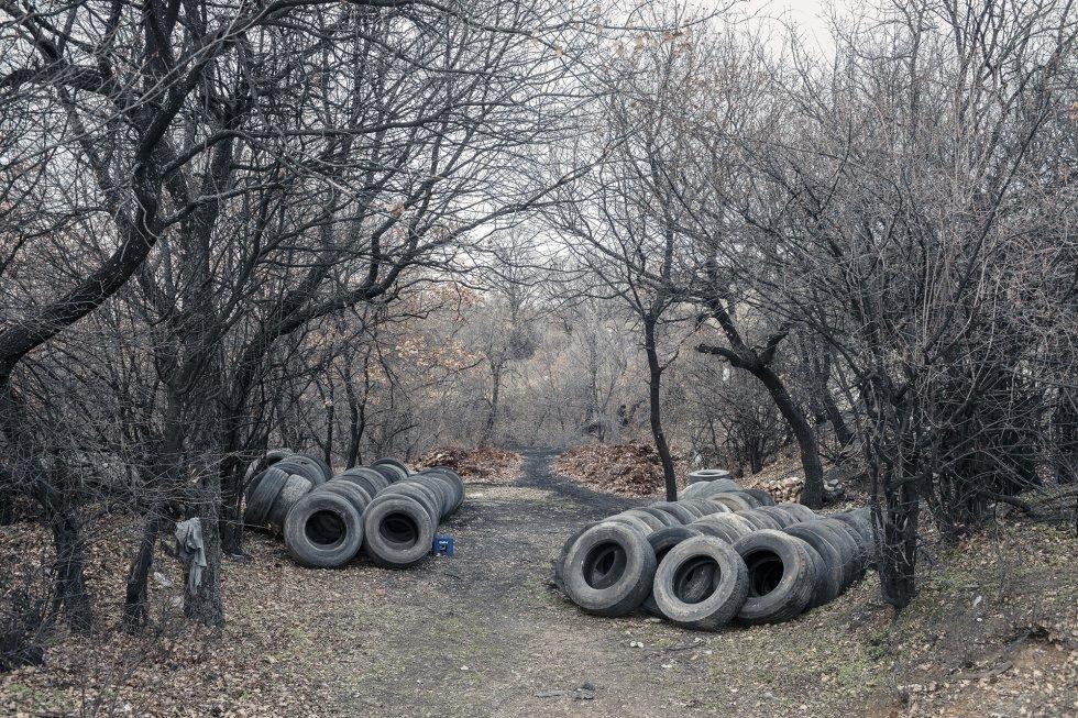 Neumáticos preparados para su quema en las colinas que rodean el pueblo de Kosturino, cerca de la ciudad de Strumica.  Los trabajadores locales dicen que prefieren quemar las ruedas porque son muy baratos. Por la carga de un camión pagan 100 euros. Para obtener 15 toneladas de producto queman entre 500 y 700 piezas. En las tiendas se puede comprar cinco kilos de cal por 2,5 euros.  rnrn El impacto de este procedimiento tradicional de producción de cal es devastador para el medio ambiente, ya que produce daños irreversibles en el ecosistema.  Según los ecologistas, las estaciones de control de la calidad del aire no alcanzan todo el país, y en muchos casos no funcionan bien. En consecuencia, las mediciones probablemente estén por debajo de las cifras reales. No hay estudios extensos y detallados sobre los grandes contaminadores de estos valles.