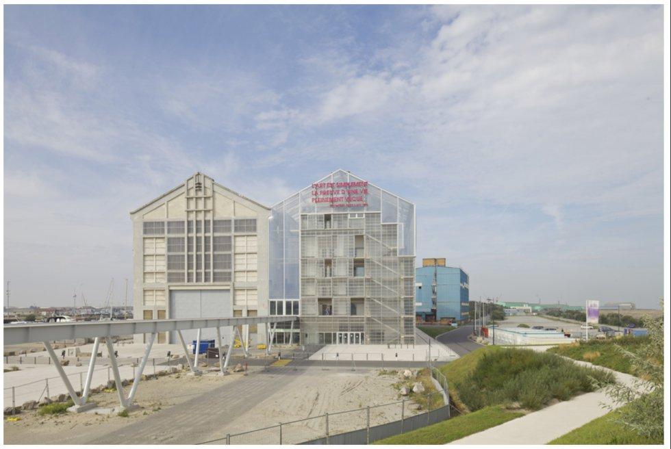 Anne Lacaton y Jean-Philippe Vassal respetaron la icónica nave portuaria de Dunkerque cuando les pidieron ampliar el Centro de Exposición de Arquitectura de Dunkerque. Mantuvieron la cubierta a dos aguas y la replicaron actualizando los materiales y aligerándolos para doblar el espacio.