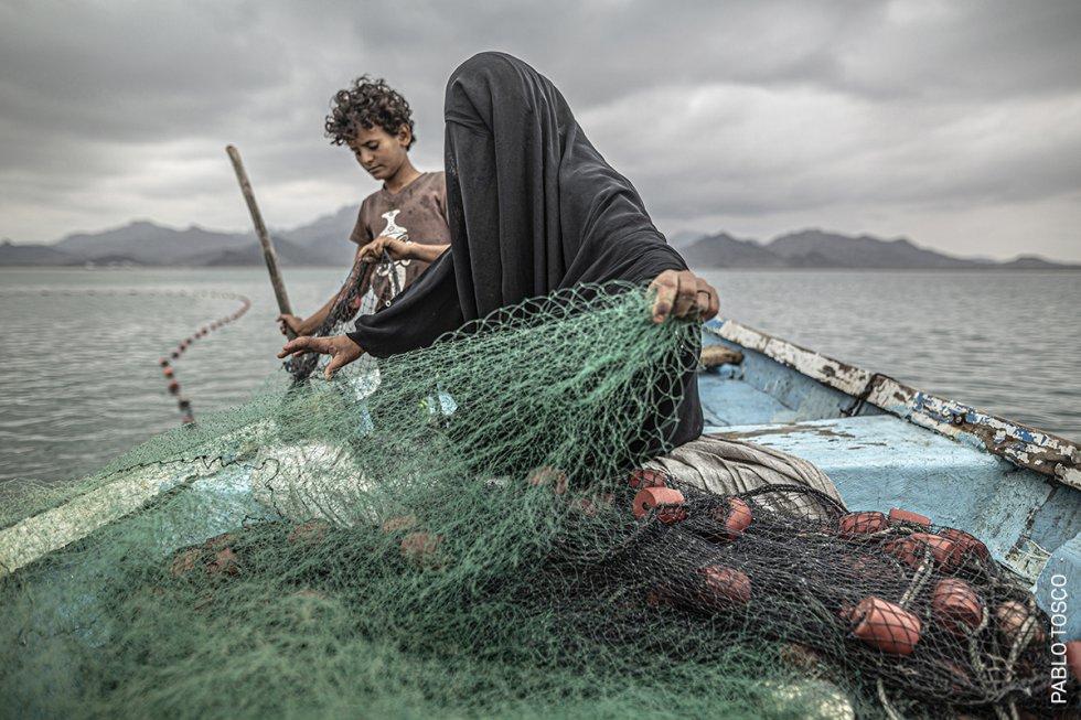 Fátima tiene nueve hijos. Para mantenerlos, se gana la vida con la pesca. A pesar de que su pueblo fue devastado por el conflicto armado en Yemen, Fátima regresó para reanudar su medio de vida, comprando una embarcación con el dinero que obtuvo de la venta de pescado. El conflicto -entre los rebeldes chiítas huthi y una coalición árabe suní liderada por Arabia Saudí- data de 2014 y ha provocado lo que UNICEF ha calificado como la mayor crisis humanitaria del mundo. Unos 20,1 millones de personas (casi dos tercios de la población) necesitaban asistencia alimentaria a principios de 2020 y aproximadamente el 80% de la población depende de la ayuda humanitaria.
