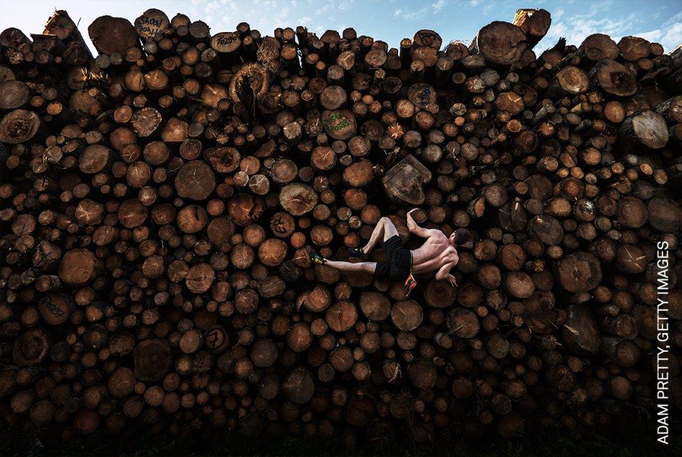 Georg sube a una pila de troncos mientras se entrena para practicar el búlder, en Kochel am See, Baviera, Alemania. El búlder consiste en escalar en pequeñas formaciones rocosas y cantos rodados de no más de seis metros de altura, sin cuerdas.