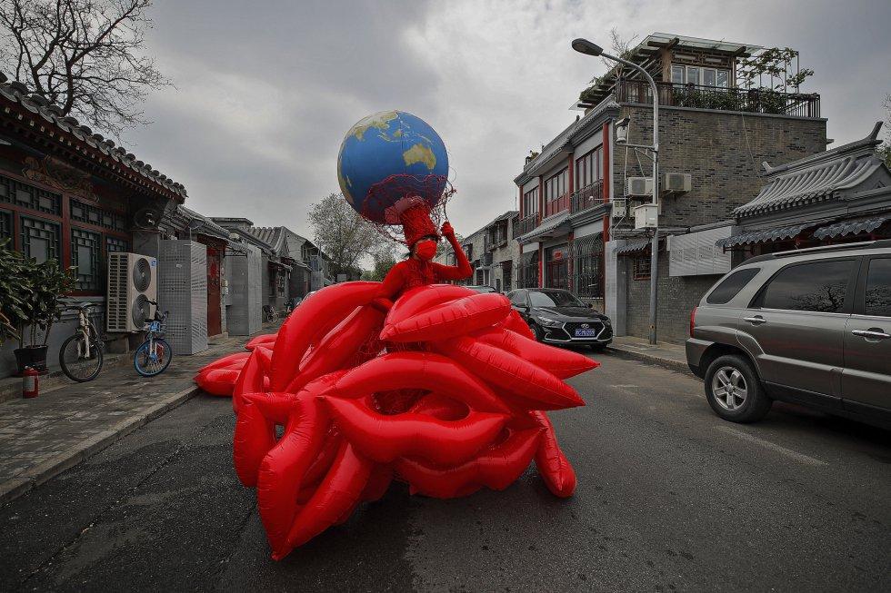 """Las alarmas no han dejado de sonar a pesar de la pandemia. Y a António Guterres, secretario general de Naciones Unidas (ONU), se le agotan las palabras duras para advertir de las consecuencias de esta crisis climática planetaria. En la imagen, la artista y activista ambiental china Kong Ning presenta su última colección de vestidos bajo el lema """"Besa la tierra"""", en una calle de Pekín."""