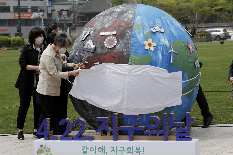La Organización Meteorológica Mundial (OMM), agencia de la ONU, lleva ya 28 años publicando sus evaluaciones anuales y la conclusión es cristalina: las evidencias e impactos del calentamiento global se agolpan. En la imagen, un grupo de activistas coloca una mascarilla a un globo representando el planeta durante un acto en el Día de la Tierra, este jueves en Seúl (Corea del Sur).