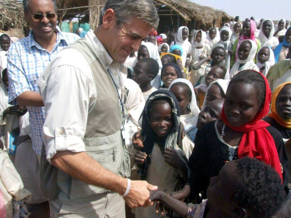 Fotografía de 2008 facilitada por la ONU y la Misión Africana en Darfur (Unamid), del actor George Clooney, designado Mensajero de la Paz por la ONU, con niños en el campo de refugiados de Zamzam, al norte de Darfur (Sudán). Clooney siempre ha mostrado una faceta humanitaria y ha estado muy comprometido con la situación de Sudán del Sur. De hecho, sus protestas le llevaron a ser detenido en 2012 y acusado de desobediencia civil por manifestarse a las puertas de la Embajada de Sudán en Washington.