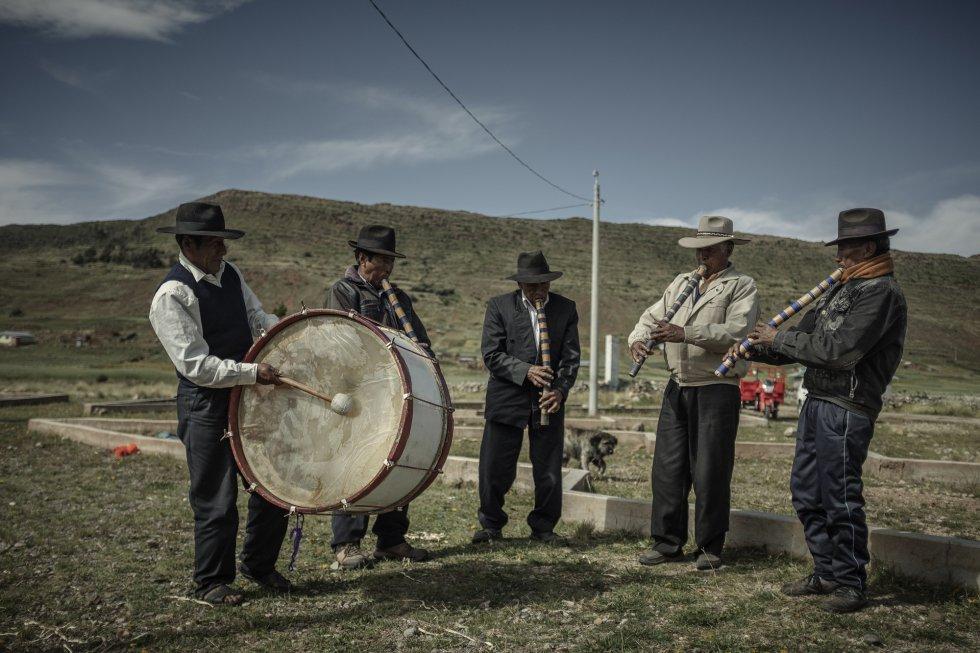 """""""La quinoa es nuestro capital"""", explica Manuel Flores Mendoza, presidente de la comunidad de Molloco. """"Nuestros antepasados la han utilizado en ceremonias por milenios"""", asegura este agricultor que cultiva su 'chacra', su campo agrícola, con técnicas ancestrales del altiplano andino y rotación de cultivo. En la imagen, varios hombres de la comunidad de Huantacachi Chila en Copaquira tocan instrumentos tradicionales por la danza que acompañan a la cosecha."""