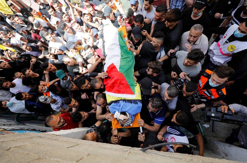 Traslado del cuerpo del palestino Hussien al-Titi, que murió durante los enfrentamientos entre las fuerzas israelíes, en el campo de refugiados de Fawwar (Cisjordania), este miércoles. Israel y Hamás se han lanzado a una guerra abierta tras dos días de hostilidades generales.