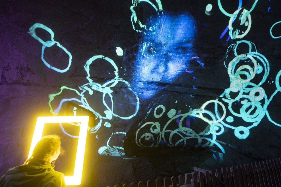 Le visage d'une jeune femme est projeté sur un mur lors du festival multivisuel Light Ragaz dans le canyon Tamina à Bad Ragaz, en Suisse.