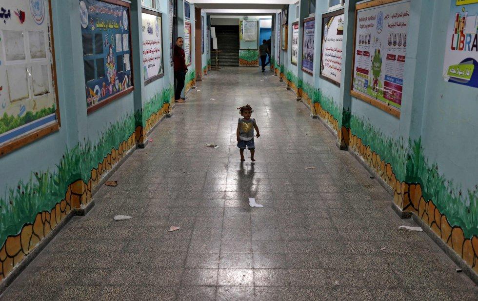 Una niña palestina camina por un pasillo de una escuela de la ONU, donde se refugió con su familia después de huir de su hogar en la ciudad de Beit Lahia.