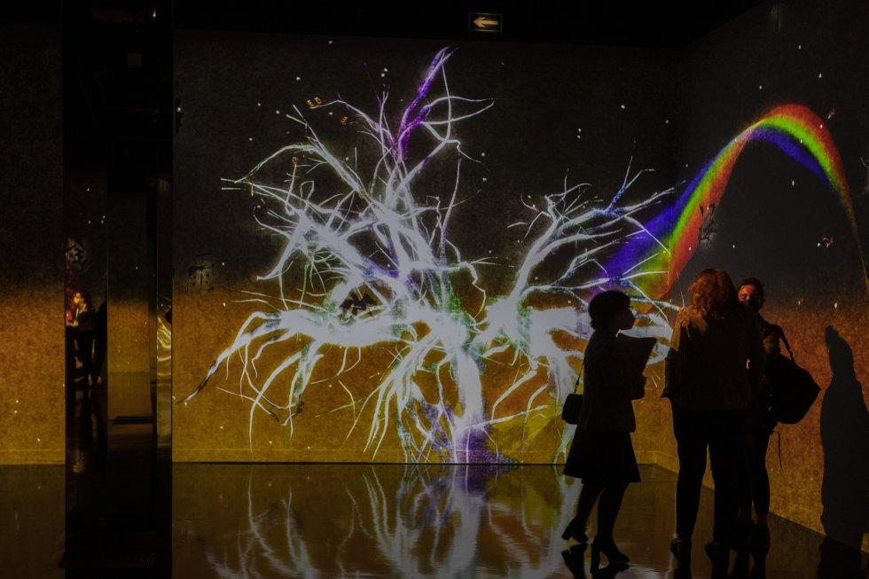 Plusieurs personnes observent le TecnoLab, l'art, la technologie et la nature, au CaixaForum Barcelona.  Cette expérience immersive et multisensorielle nous invite à repenser notre relation avec ce qui nous entoure.